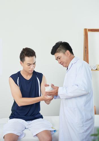 Un profesional de la salud examina la muñeca de un paciente