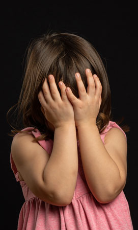 Una niña se tapa la cara mientras llora